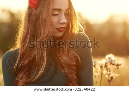 Young, beautiful, attractive model woman in swimsuit, posing in a field of flowers on the background of sunset, hairstyle, makeup, red corolla with flowers, eyes looking down, portrait. - stock photo