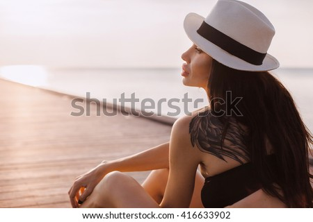 young beautiful attractive woman standing alone on pier in luxury resort hotel, summer vacation,brunette hair, sexy apparel, tropical beach, seductive, sensual, smiling full lips,enjoying day - stock photo