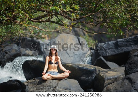 Young, beautiful authenticity woman, of European appearance, meditating in the lotus position on a large stone near mountain river. The practice of yoga outdoors. Yoga-lifestyle - stock photo