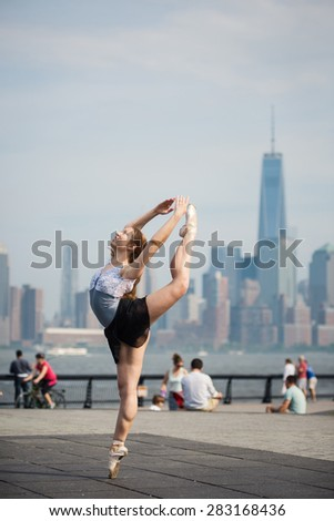 Young beautiful ballerina dancing along the New Jersey waterfront with New York skyline in the background. Ballerina Project.