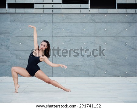 Young beautiful ballerina dancing outdoors in a modern environment. Ballerina Project. - stock photo