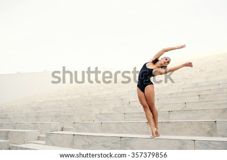 Young beautiful ballerina dancing outdoors in a modern environment. Ballerina Project. Filtered image. - stock photo