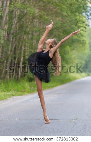Young beautiful ballerina dancing outdoors in a parkway with trees.  - stock photo