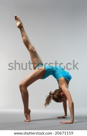 young beautiful ballerina posing on grey background - stock photo