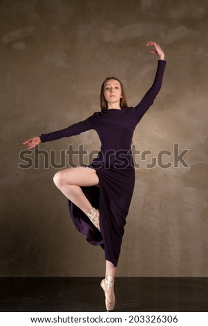 young beautiful ballet dancer in long dress posing on studio background
