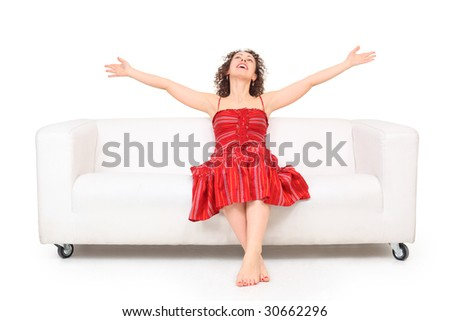 Young beautiful barefooted woman in red dress with hands up sits on white leather sofa - stock photo