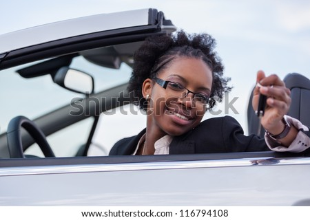 Young beautiful black woman driver holding car keys driving her new car