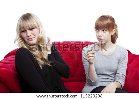 young beautiful blond and red haired girls is disgusting because of smoker on red sofa in front of white background - stock photo