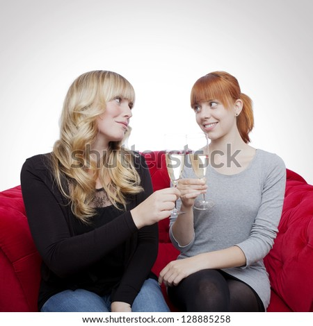 young beautiful blond and red haired girls with champagne on red sofa in front of grey background