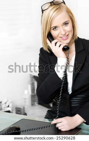 Young beautiful blond businesswoman recieving call in a secratary job