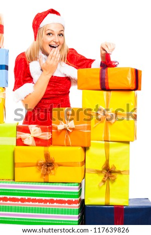 Young beautiful blond cute happy woman in Santa costume opening Christmas gift boxes, isolated on white background. - stock photo
