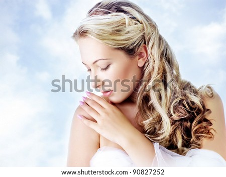 young beautiful blond female with long hair, on background of sky. - stock photo