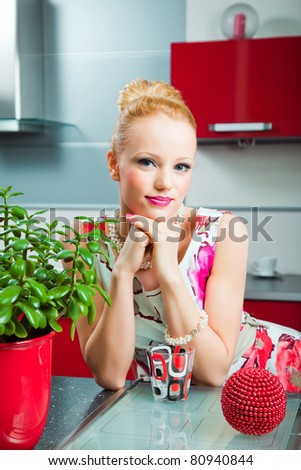 young beautiful blond girl wearing white and pink dress with glass in interior of red modern kitchen