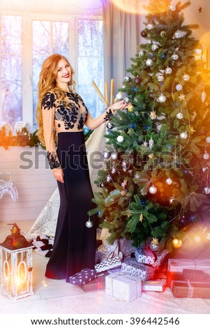 Young beautiful blond girl, woman in a beautiful room with a Christmas tree, a Christmas tree, a girl with gifts, gold tree, golden hair, happy woman new year