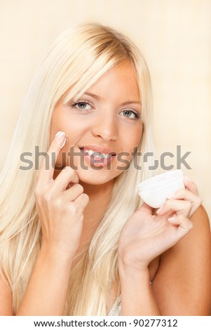 Young beautiful blond hair woman applied face cream - stock photo