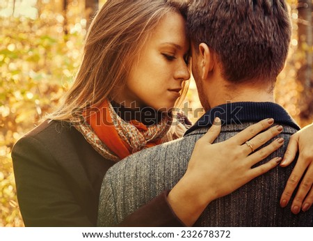 Young beautiful blond woman embraces a man in autumn park, tenderness scene