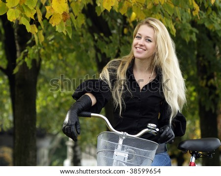Young beautiful blond woman on bicycle under maple tree. Fall