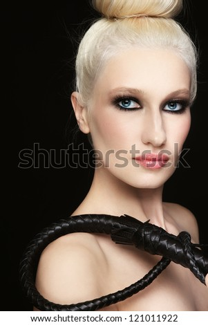 Young beautiful blond woman with braided bull whip in her hand - stock photo