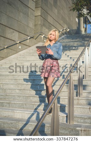 Young beautiful blonde caucasian girl using a tablet connected online on a staircase outside in the city wearing jeans shirt and floral skirt - technology, communication, social network concept - stock photo
