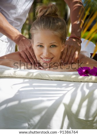 Young beautiful blonde caucasian woman gets massage and beauty treatment in luxury resort - stock photo