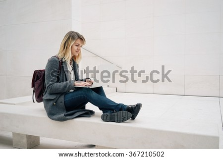 young beautiful blonde female student using laptop computer while sitting on the stone bench. copy space area for your text message or content - stock photo