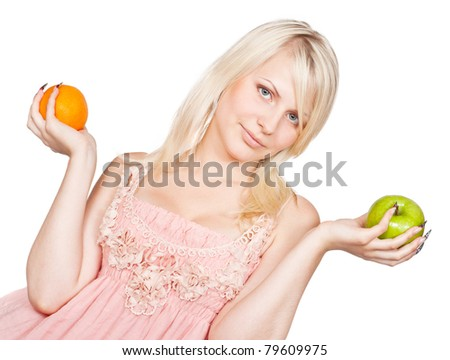 Young beautiful blonde girl choosing between apple and orange. Isolated on white background