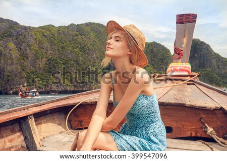 Young beautiful blonde girl cruising on retro wood boat by Andaman sea and behind her you can see Ko Phi Phi Lee Island. Dressed in beautiful blue dress and wearing straw hat. - stock photo