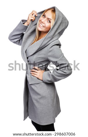 Young beautiful blonde girl in a long gray of thick cloth coat with large hood  - stock photo