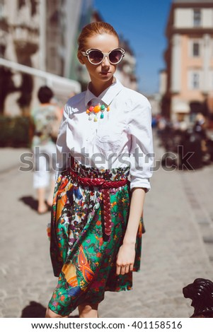 young beautiful blonde girl in a white shirt and a green skirt fashionable in sunglasses posing in the city center on the street of a European capital, Paris, pavement, people on the street portrait - stock photo