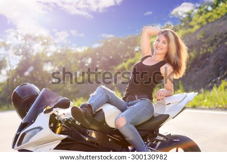 Young beautiful blonde girl in trendy jeans and a black t-shirt is resting on nature in seat of modern motorcycle. Outdoor portrait in soft sunny tones. - stock photo