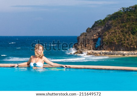 Young beautiful blonde girl is in the pool. Tropical sea in the background. Summer vacation. - stock photo