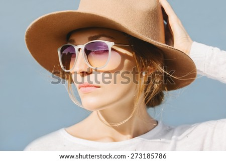 Young beautiful blonde girl sunbathing near the water. Wearing hat and sunglasses. Outside - stock photo