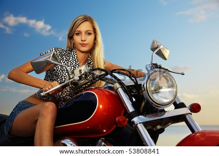 young beautiful blonde outdoors, posing with red motorcycle. sky on background. - stock photo