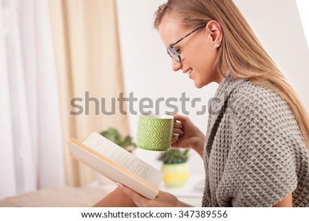 young beautiful blonde sitting on a bed and reading a book