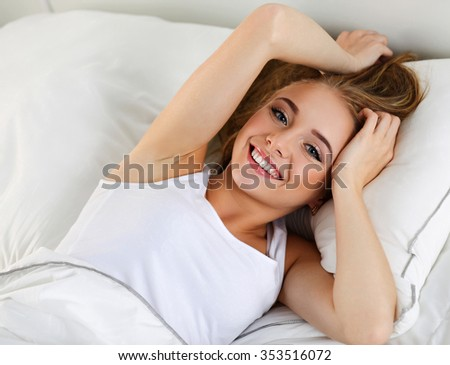 Young beautiful blonde smiling woman portrait wake up early morning after sleeping and lying in bed. Top view. Sweet dreams and good morning, new day, weekend, day off, holidays concept - stock photo