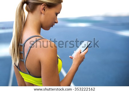 Young beautiful blonde sportswoman on racetrack outdoors. Fit woman using mobile phone - stock photo