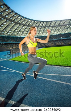 Young beautiful blonde sportswoman running on racetrack outdoors. Fit woman is at large nice modern stadium - stock photo