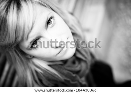 Young beautiful blonde staring at camera from below - stock photo