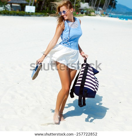 Young beautiful blonde tanned sexy woman goes crazy and jumping having fun on the beach in summer vacation time on white sand beach  - stock photo