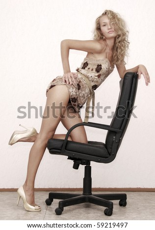 young beautiful blonde with leather armchair - stock photo