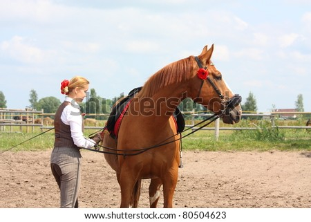 Young beautiful blonde woman and chestnut danish warmblood horse