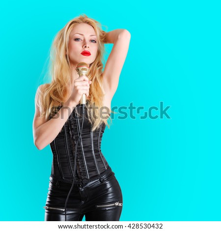 Young beautiful blonde woman hold microphone in her hands
