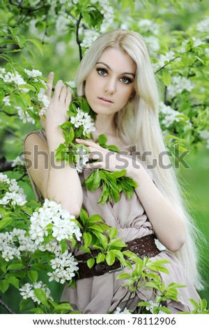 Young beautiful blonde woman in a dress in blooming apple garden - stock photo