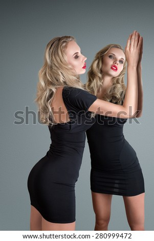 Young beautiful blonde woman in black mini dress with mirror reflection - stock photo