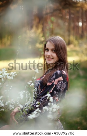 Young beautiful blonde woman in blooming garden. - stock photo