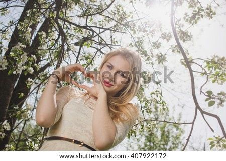 Young beautiful blonde woman in blooming garden. Delicate girl enjoys spring nature - stock photo