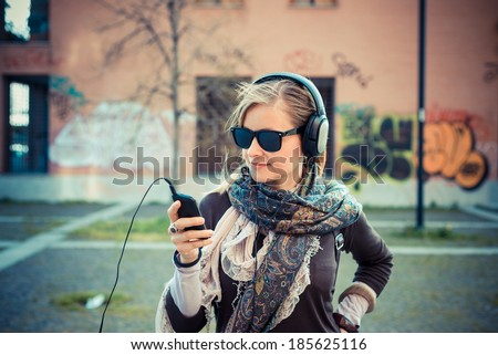 young beautiful blonde woman listening to music in the city - stock photo
