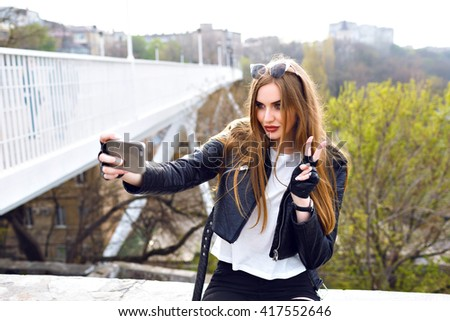 Young beautiful blonde woman making selfie near city urban bridge, sending air kiss, hipster brutal style, leather jacket and gloves, traveling mood. - stock photo