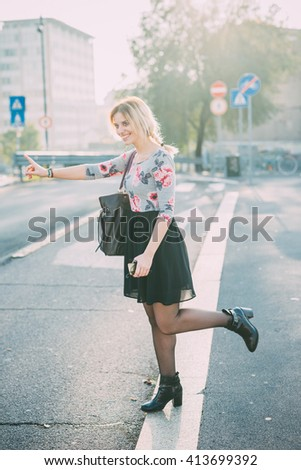 Young beautiful blonde woman outdoor in the city back light hitchhiking, holding a smart phone - travel, technology, transport concept - stock photo