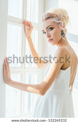Young beautiful blonde woman posing in a white Studio. The portrait with the light from the window. Amazingly beautiful eye color.